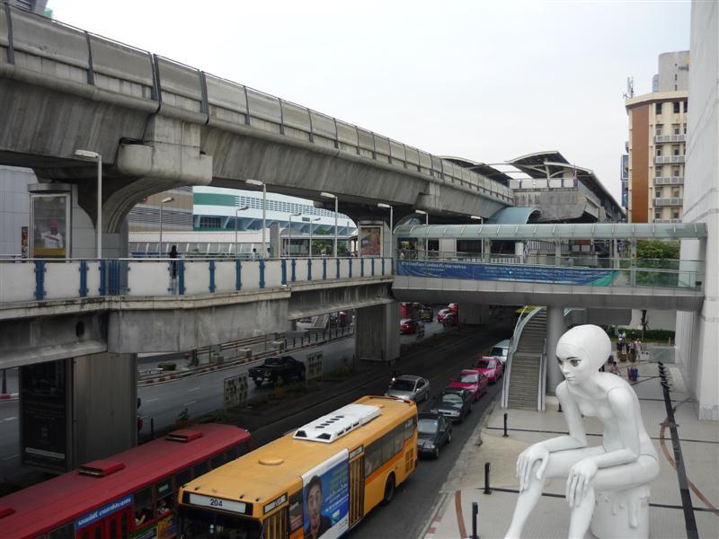 Pohled na ulici Thanon Rama I. V horním patře jezdí vlaky Skyline, pod ním je Sky Walk pro pěší, dole jezdí auta. Obří socha patří k budově Bangkok Art and Culture Cetre.