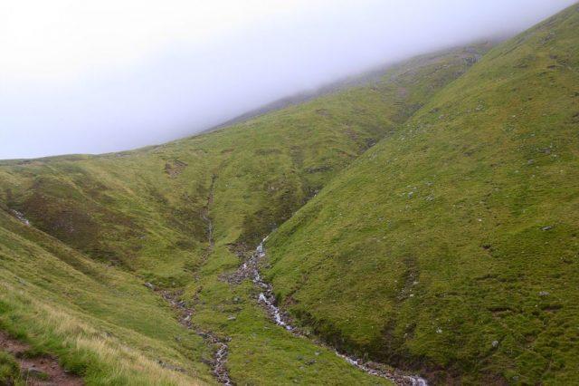 Sedlo mezi Meall an t-Suidhe a Ben Nevis, v pozadí cesta na Ben Nevis zahalená mlhou.