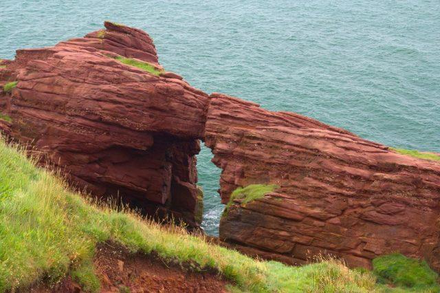 Skalní okno Needle's eye na útesech Seaton Cliffs severně od města Arbroath