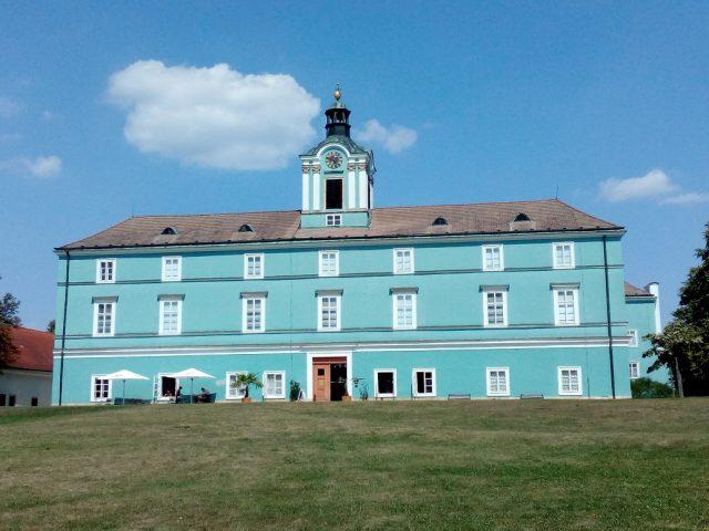 Modrá fasáda dačického zámku září ve slunci